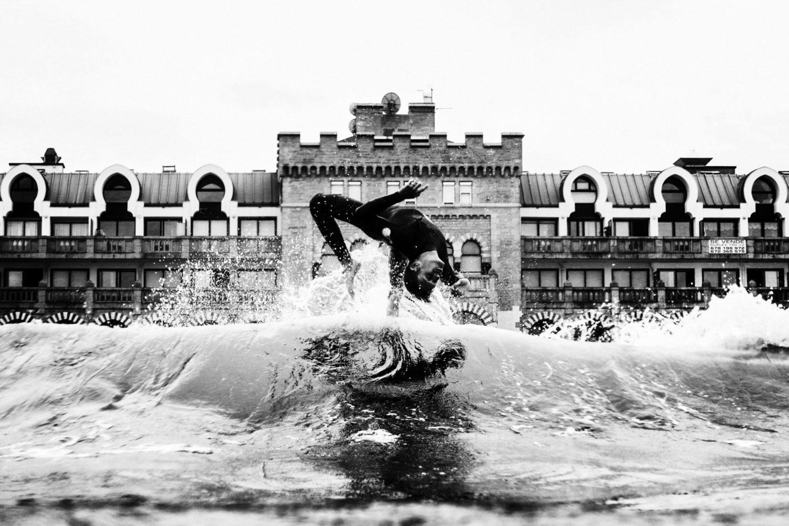 Saut d'un surfeur à la plage d'hendaye, deriere, l'ancien casino de la ville qui se situe au bord de l'eau